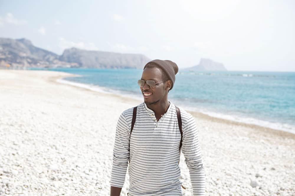 happy-young-afro-american-traveler-stylish-hat-sunglasses-having-nice-walk-along-seashore-enjoying-sunny-weather-beautiful-views-attractive-young-black-man-posing-sea-scenery