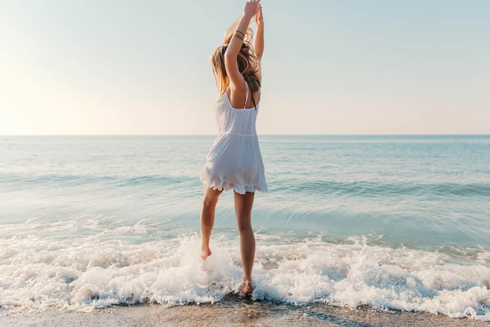 young-attractive-happy-woman-dancing-turning-around-by-sea-beach-sunny-summer-fashion-style-white-dress-vacation