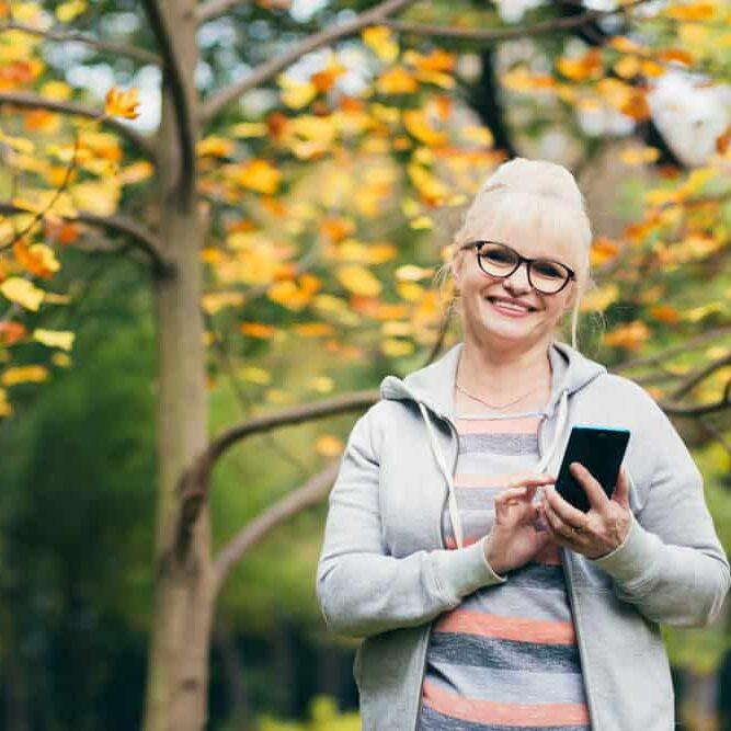 beautiful-senior-woman-backpack-walk-park-talking-phone
