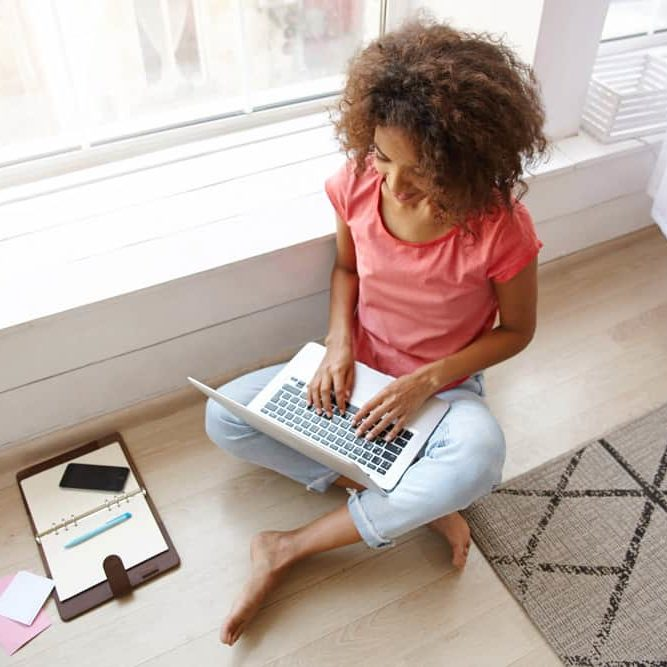 indoor-shot-young-dark-skinned-female-with-brown-curly-hair-sitting-floor-with-crossed-legs-writing-e-mail-with-her-modern-laptop