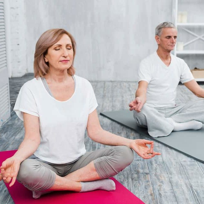 senior-couple-performing-meditation-exercise-mat-home